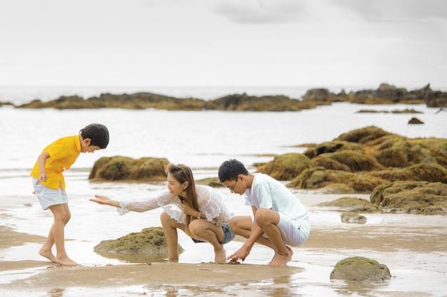 Drie mensen aziatische familie op vakantie, moeder en twee zonen spelen en leren voor nieuwe ervaring op tropisch strand naast de groep rock