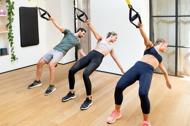 Drie mensen die machtstrekkracht met trx opleiden bij gymnastiek