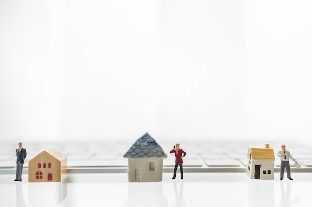 Drie mensen die van het zakenman miniatuurcijfer zich en met huisstuk speelgoed en computertoetsenbord bevinden werken.