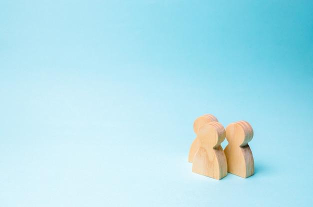 Drie mensen staan samen en praten. twee houten figuren van mensen voeren een gesprek