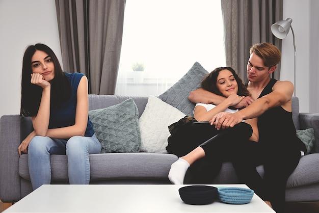 Drie mensen zitten op de bank, twee knuffelen, de derde verveelt zich
