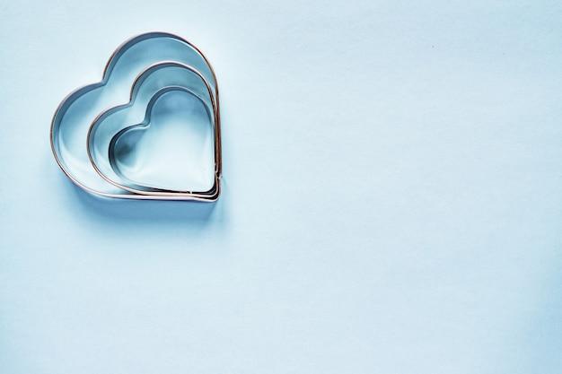 Drie metaalkoekjessnijders in hartvorm op lichtblauwe achtergrond met exemplaarruimte