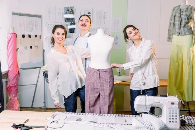 Drie modeontwerpers of kleermakers glimlachen naar de camera en meten handgemaakte broek op een mannequin in gezellige atelierstudio. naaister, kleermaker, mode en showroom concept