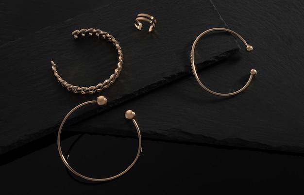 Drie moderne armbanden en dubbele vormring op zwarte stenen dienbladen met kopieerruimte