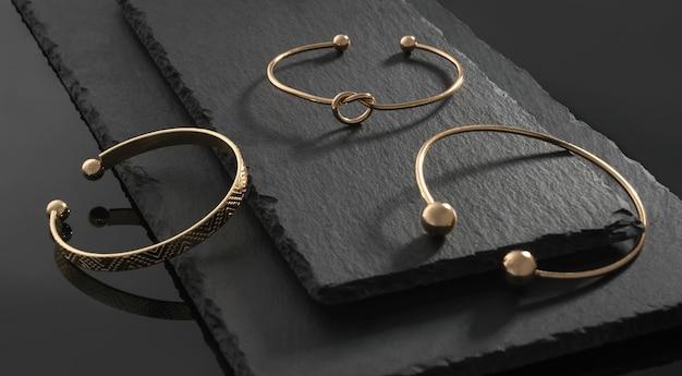 Drie moderne design gouden armbanden op natuurstenen platen