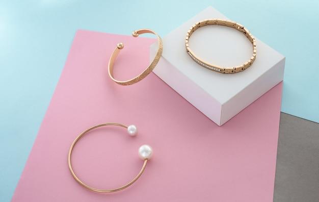 Drie moderne gouden armbanden op pastelkleurenpapieren achtergrond met kopieerruimte