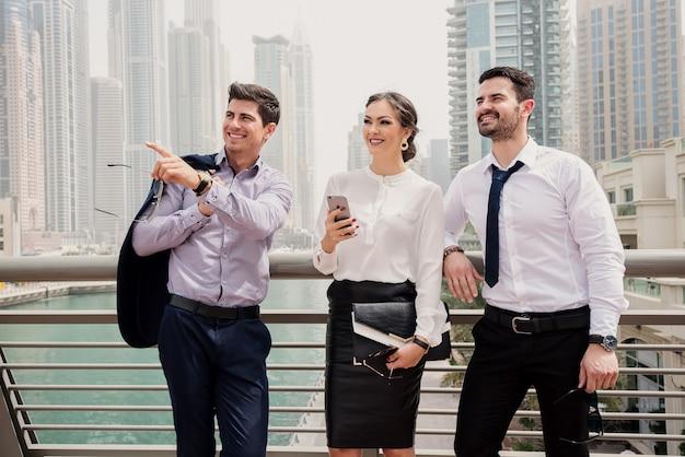 Drie moderne hogescholen staan en kijken op een nieuwe bedrijfslocatie.