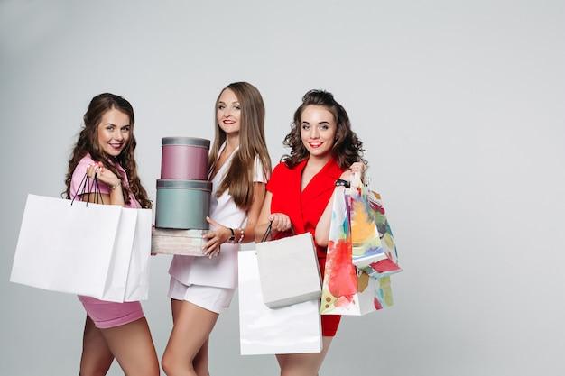 Drie modieuze dames met boodschappentassen en dozen.