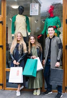 Drie modieuze vrienden die zich voor de holding van de venstervertoning het winkelen zakken bevinden