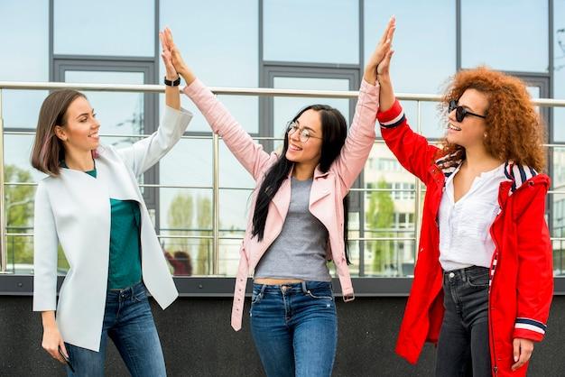 Drie modieuze vrouwelijke vrienden die hoge vijf geven in openlucht