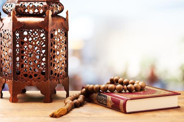 Drie months.islamic holy book quran met rozenkrans kralen onder zacht licht.
