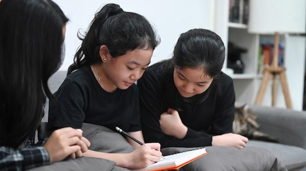 Drie mooie aziatische kinderen die thuis online les studeren.