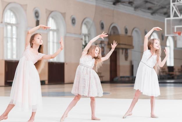 Drie mooie ballerinameisjes die in dansklasse dansen