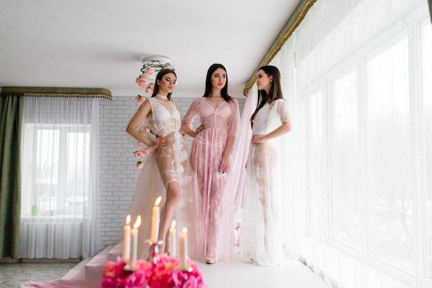 Drie mooie bruid in luxe kanten gewaden in de kamer met een delicaat decor