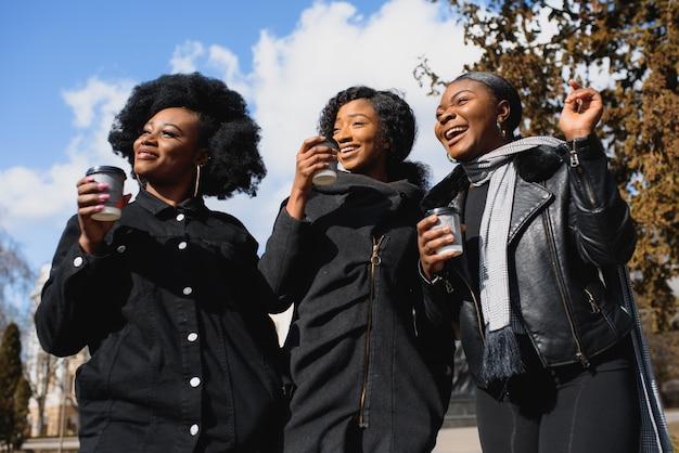 Drie mooie donkere meisjes met lang haar staan in een stad en drinken koffie