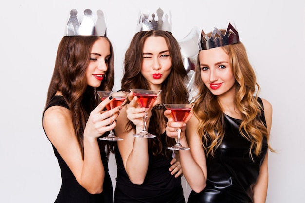 Drie mooie elegante vrouwen vieren vrijgezellenfeest en drinken cocktails. beste vrienden in zwarte avondjurk, kroon op kop en gerinkelglazen. lichte make-up, rode lippen. binnen.