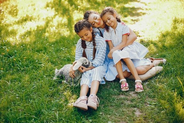 Drie mooie en schattige meisjes in blauwe jurken met mooie kapsels en make-up zitten