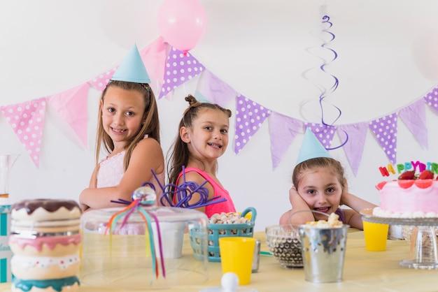 Drie mooie glimlachende meisjes die bij verjaardagspartij stellen