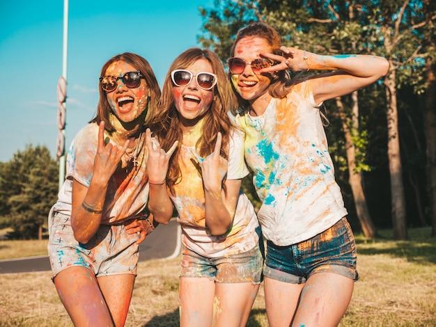 Drie mooie glimlachende meisjes poseren op holi party
