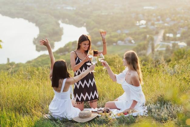 Drie mooie jonge dames hebben samen plezier en drinken witte wijn op een hete zomerdag.