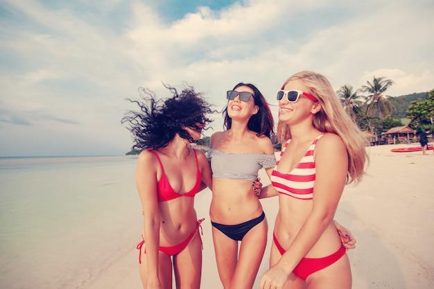 Drie mooie jonge europese slanke vriendinnen in felrode en gestreepte bikini's lopen op een tropisch strand op vakantie, geluk vreugde zomer en plezier