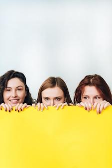 Drie mooie jonge meisjes die voor de camera stellen