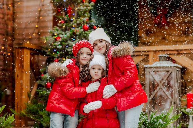 Drie mooie jonge meisjes in rode en witte winterkleren poseren in de achtertuin met sneeuwt en kerstdecor.