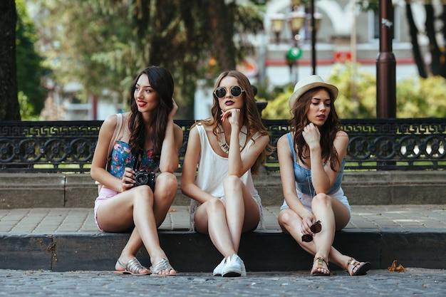 Drie mooie jonge meisjes poseren tegen van het park