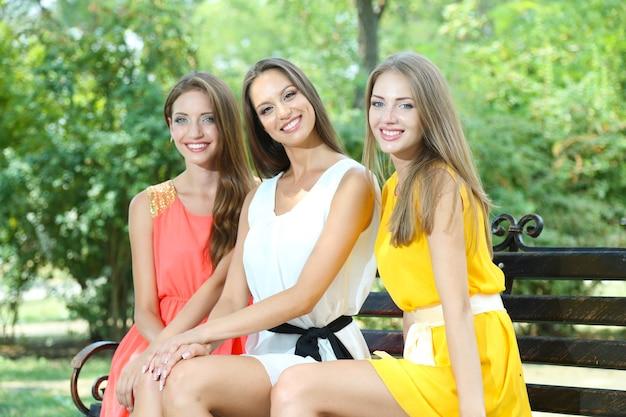 Drie mooie jonge vrouw zittend op een bankje in het zomerpark