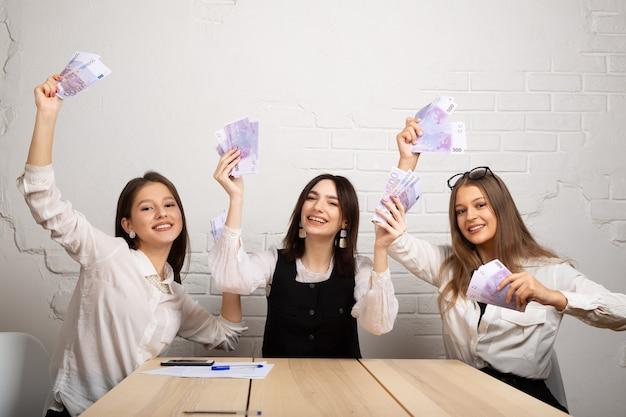 Drie mooie jonge vrouwen aan de tafel in het kantoor met eurogeld