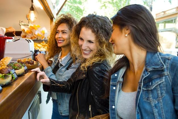Drie mooie jonge vrouwen bezoeken eten markt in de straat.