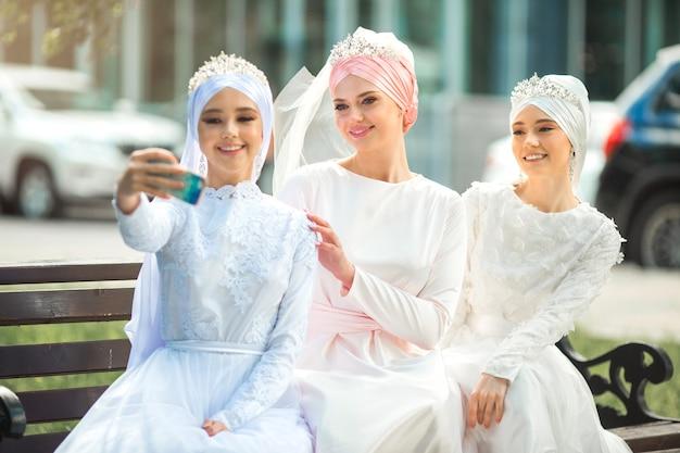 Drie mooie jonge vrouwen in feestelijke moslimjurken nemen een selfie aan de telefoon