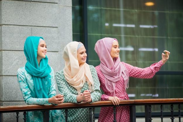 Drie mooie jonge vrouwen in moslimjurken worden aan de telefoon gefotografeerd