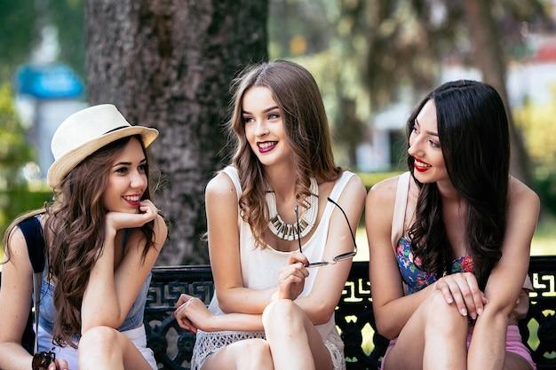Drie mooie jonge vrouwen poseren tegen de achtergrond van het park