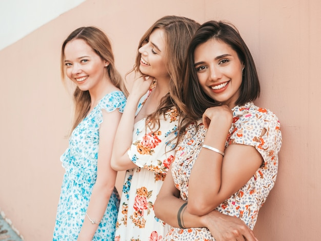 Drie mooie lachende meisjes in trendy zomer sundress poseren op straat