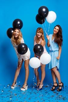 Drie mooie meisjes die bij partij over blauwe muur rusten
