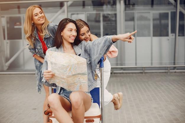 Drie mooie meisjes die zich bij de luchthaven bevinden