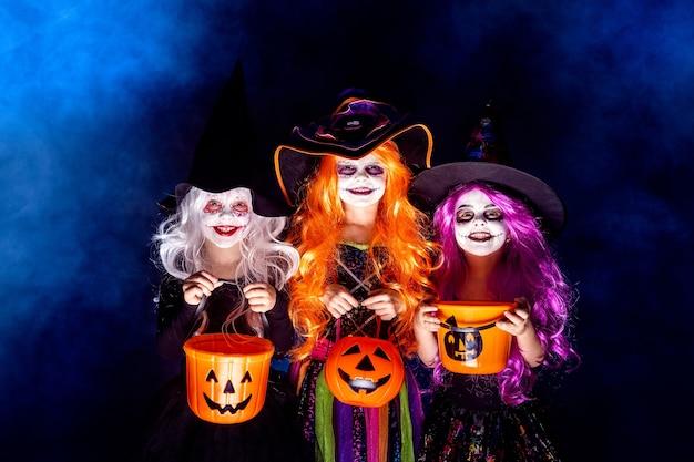 Drie mooie meisjes in een heksenkostuum op een donkere achtergrond in rook.