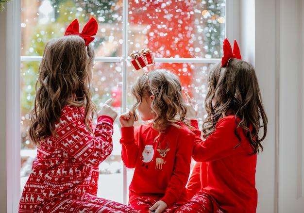 Drie mooie meisjes in rode kerstpyjama's en hoofdbanden die bij het grote raam zitten met buiten sneeuwt.