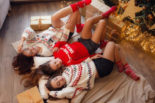 Drie mooie meisjes liggen in de buurt van de kerstboom te wachten op geschenken. jonge vrouw beste vrienden die kerstmis in huis vieren. prachtige gouden kerstversiering op een hoge kerstboom
