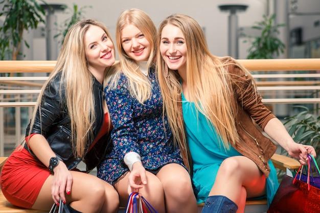 Drie mooie meisjes met boodschappentassen