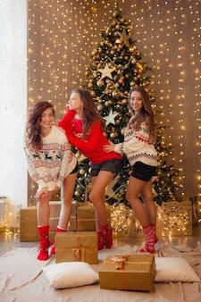 Drie mooie meisjes op oudejaarsavond. jonge vrouw beste vrienden die kerstmis in huis vieren. plezier vriendschap eindigt nooit concept. prachtige gouden kerstversiering op een hoge kerstboom