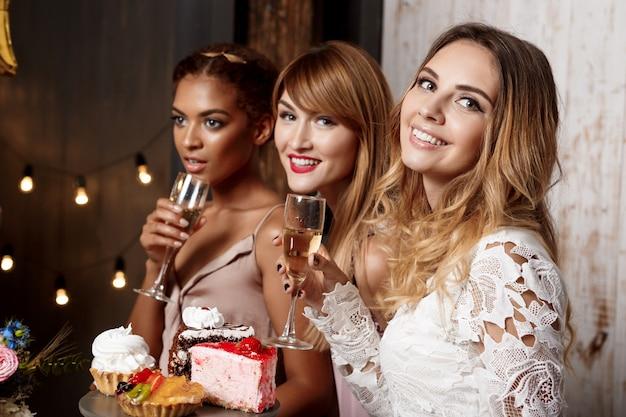 Drie mooie meisjes rusten op feestje.