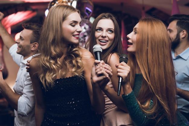 Drie mooie meisjes zingen in een karaokeclub