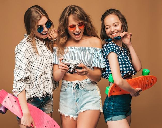 Drie mooie stijlvolle lachende meisjes met kleurrijke penny skateboards. vrouwen in de zomer geruite shirt kleding. foto's maken met een retro fotocamera
