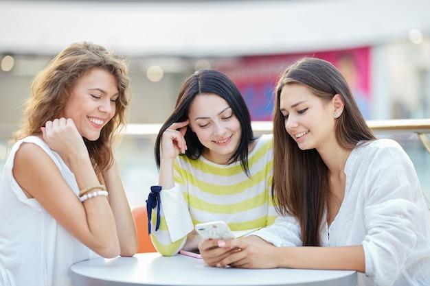 Drie mooie stijlvolle meisjes zitten aan een tafel in een café in het moderne winkelcentrum en kletsen na het winkelen.