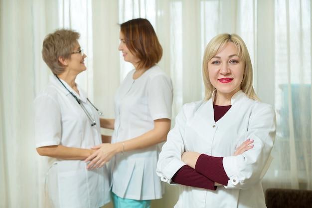 Drie mooie volwassen vrouwen in witte medische jassen