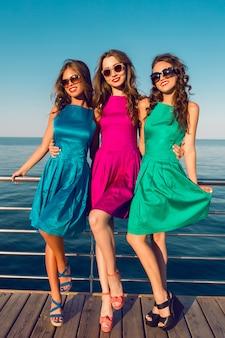 Drie mooie vrienden in dezelfde kleurrijke jurken poseren in de buurt van het strand