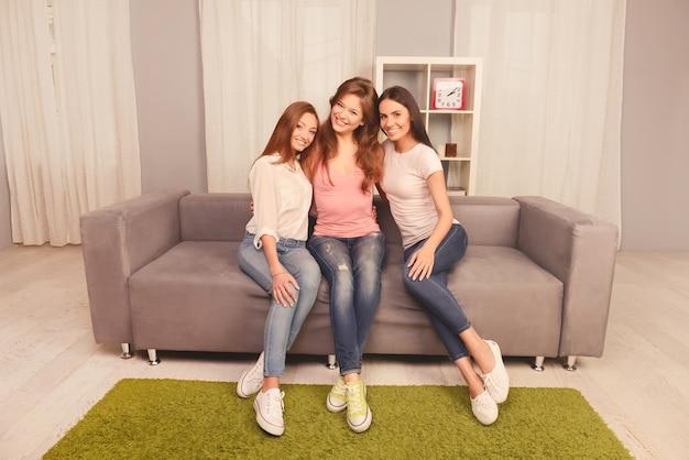 Drie mooie vriendinnen zitten in een omhelzing op de bank