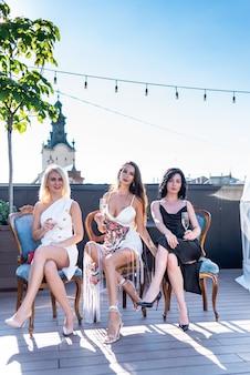 Drie mooie vrouw vieren en koelen met champagne op terras